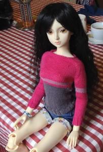 Kimiko wearing a pink and grey striped merino wool sweater.