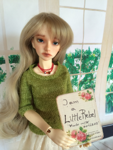 Heather wearing her grassy green peplum top and showing the placard for a BJD competition from LittleRebel.