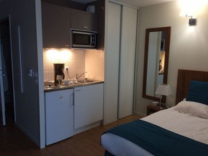 Inside view of 20m2 aparthotel room with kitchenette and double bed.